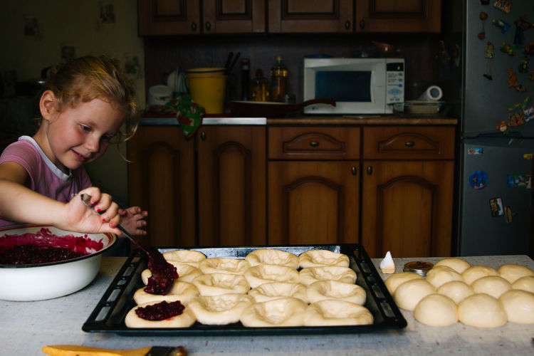 A girl prepares pies with lingonberries in the kitchen