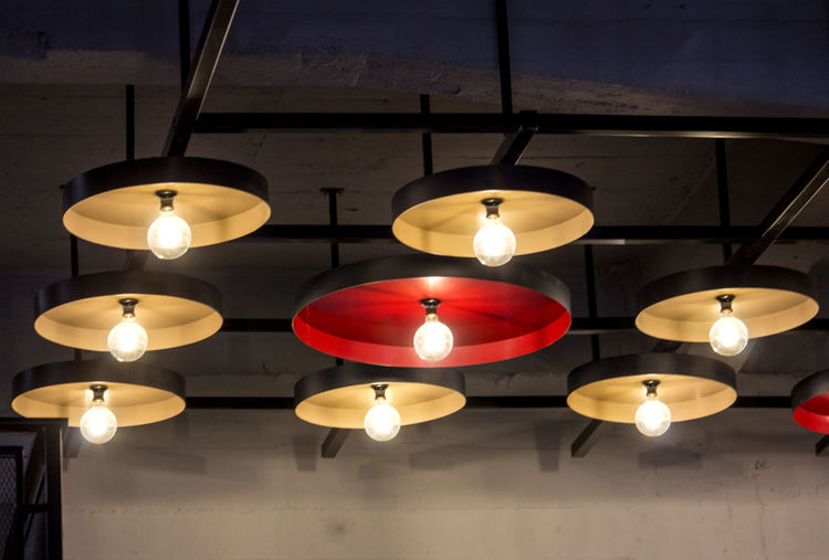 Low angle view of illuminated pendant lights hanging from ceiling