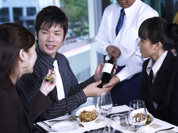 Colleagues with drinks at restaurant during meeting