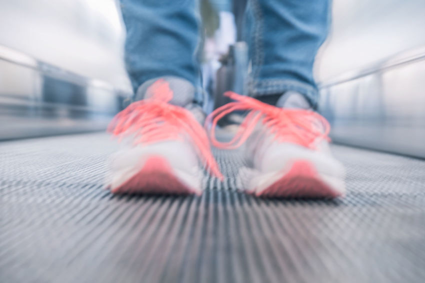 Adult Blurred Motion Casual Clothing Close-up Copy Space Day Escalator Human Body Part Human Foot Human Leg Indoors  Jeans Lifestyles Long Exposure Low Section Motion One Person People Pink Color Shoe Shoelace Sports Shoe