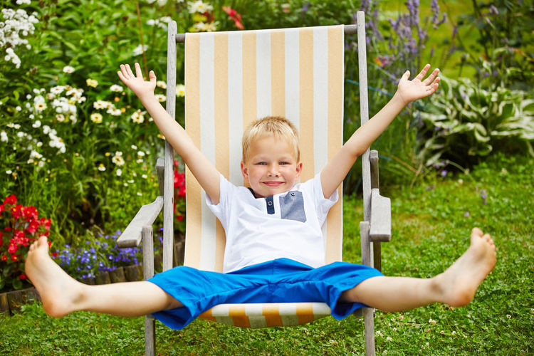 Portrait of cheerful boy sitting on deck chair at park