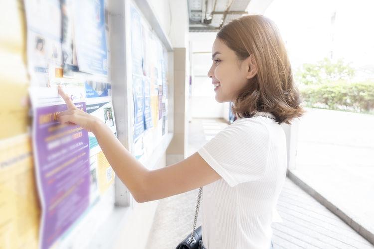 Woman reading document on bulletin board in corridor