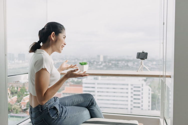 Young woman using mobile phone while sitting on window