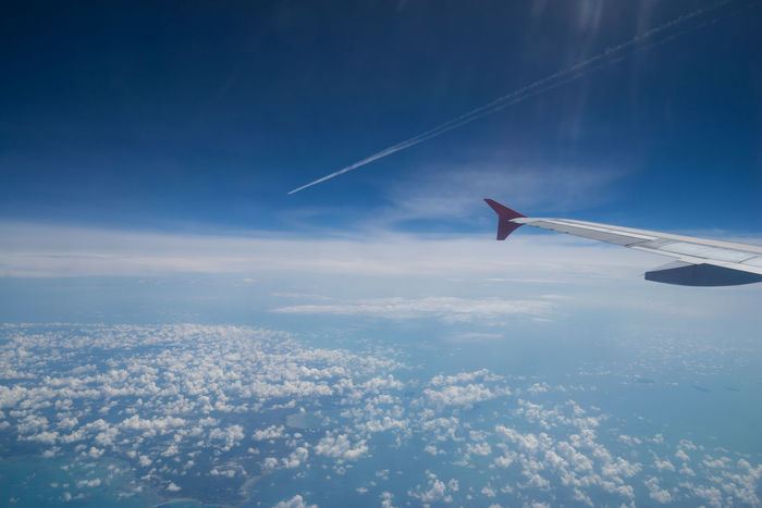 View from a jet plane window over Lombok island, Indonesia Above The Clouds Aerial View Aeroplane In The Sky Blue Sky Clouds Contrails Flight Window Wing Of Plane