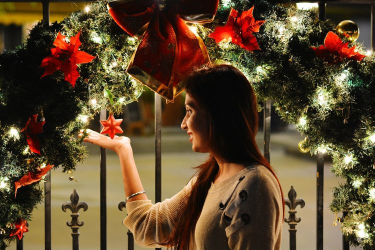 Side View Of Smiling Young Woman Standing By Christmas Tree At Night