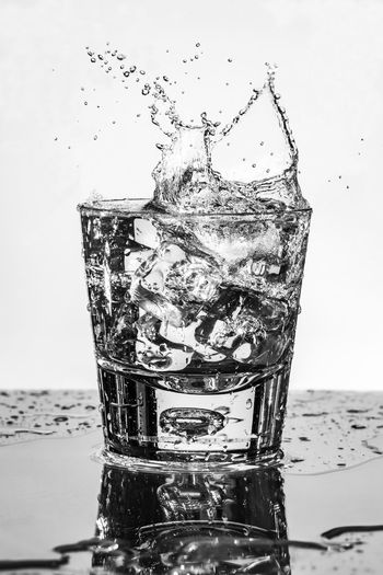 Close-up of water splashing in glass against white background