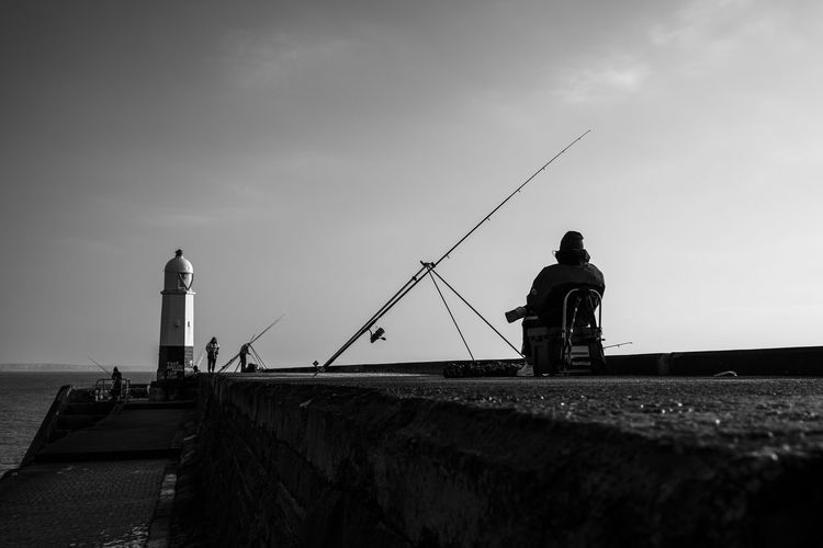 Lighthouse Beauty In Nature Cloud - Sky Day Dramatic Scene Fisherman Fishing Lighthouse Men Monochrome Nature One Person Outdoors Pastime People Real People Sky Standing Waitng Water