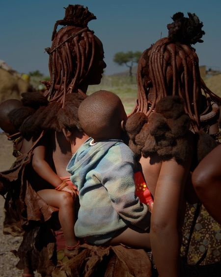 Himba mothers carrying children in desert