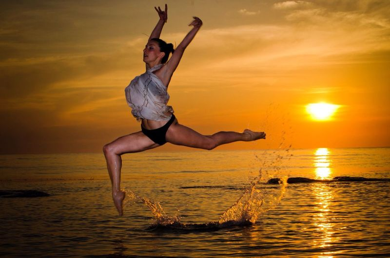 Beautiful Woman Performing Gymnastics In Sea Against Orange Sky During Sunset