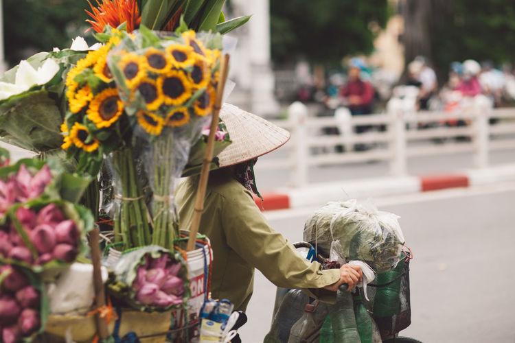Rear view of man selling flowers on street