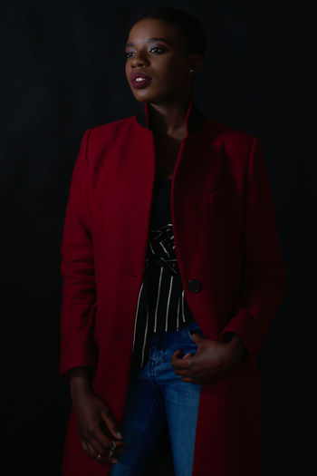 Woman In Red Jacket Standing Against Black Background