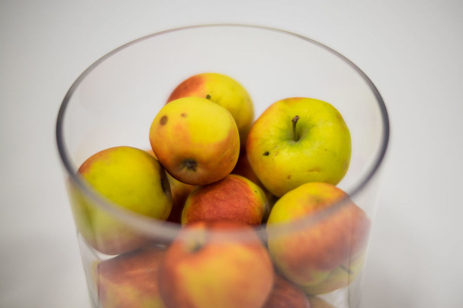 A glass bowl with apples placed on white table Apple Apples Bowl Fruit Glass Glass Jar Red Table White Background Yellow