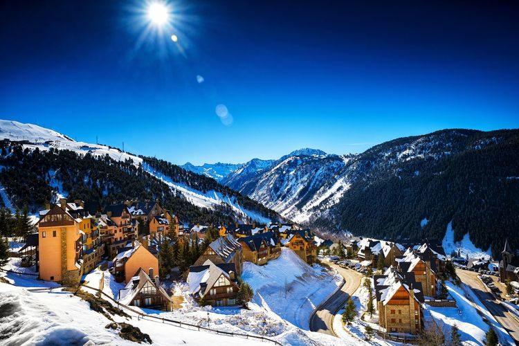 Scenic view of snow covered mountains against blue sky