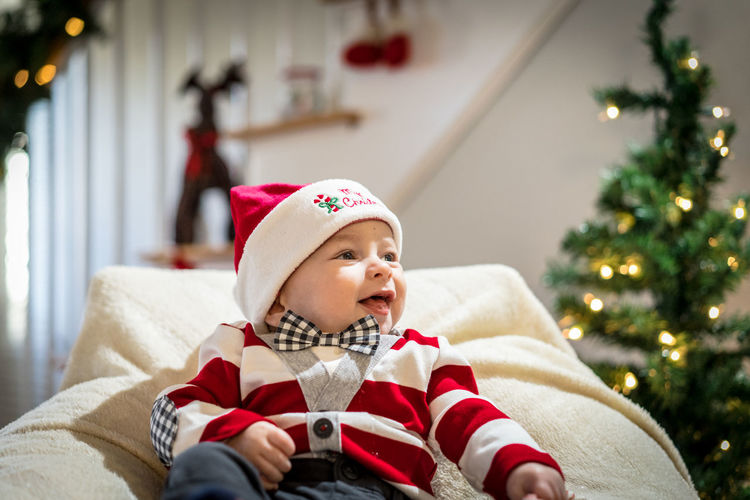 Smiling baby boy on chair against christmas decoration at home