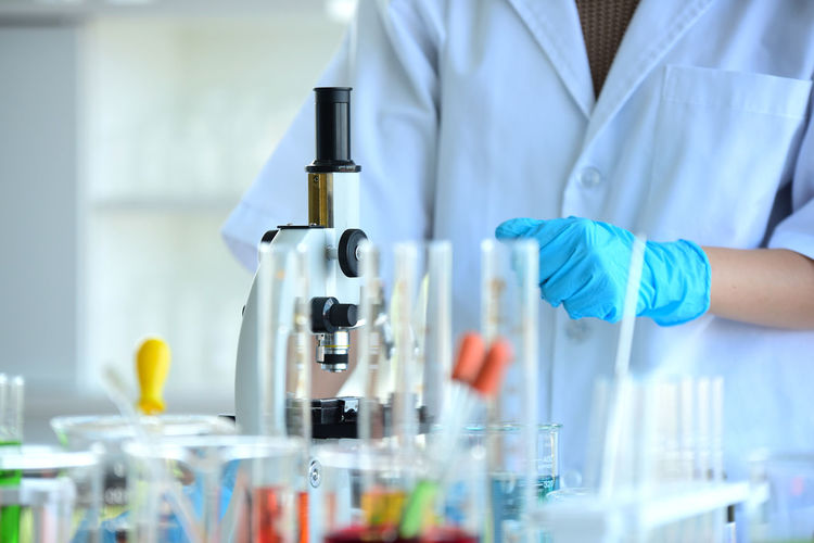Midsection of scientist standing by microscope at laboratory