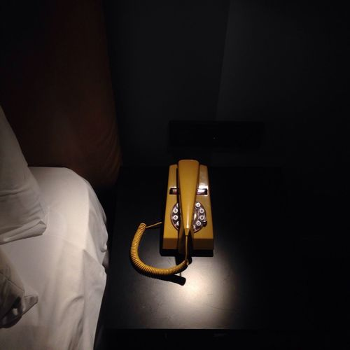 High angle view of old-fashioned yellow telephone by bed on table