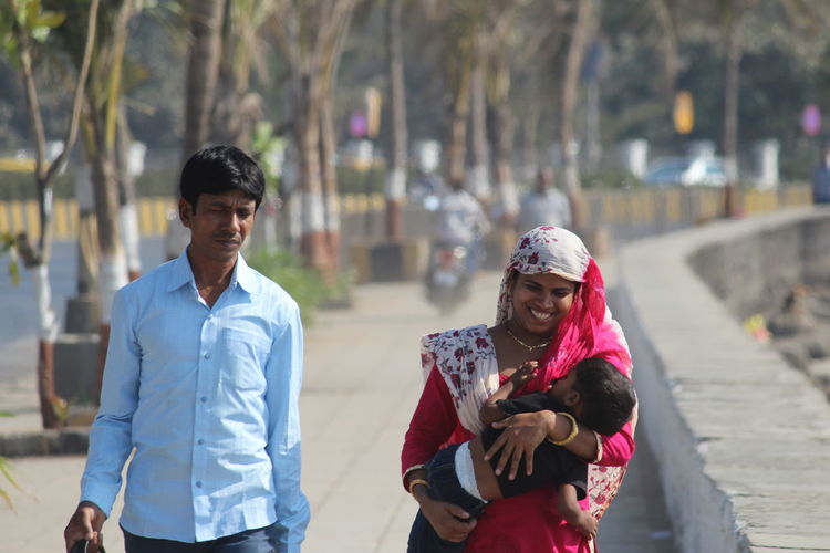 Parents with child walking on footpath in city