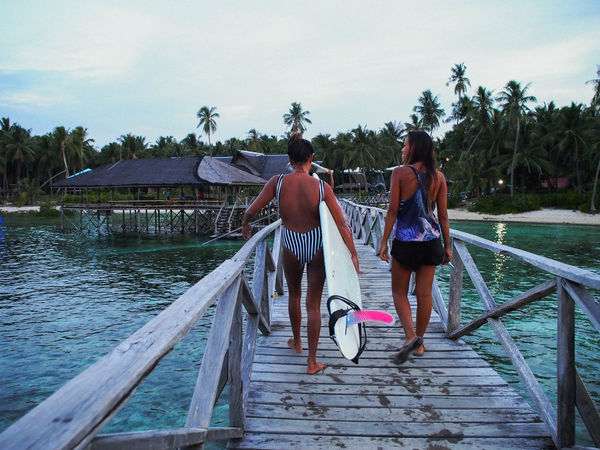 Girls getting out of the surf in Siargao Blue Longboard Longboard Girl Nature Ocean Palm Trees Philippines Pier Surf Surfing Vacations Water First Eyeem Photo