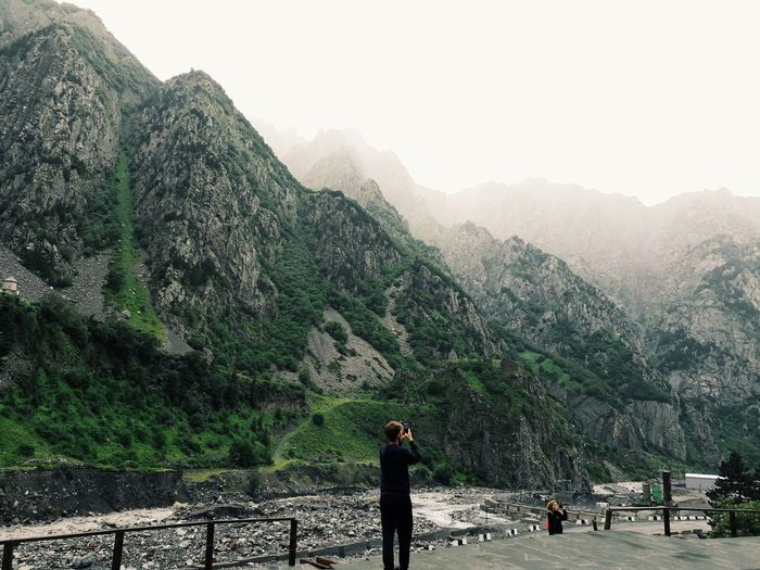 Man clicking photograph of mountains against clear sky