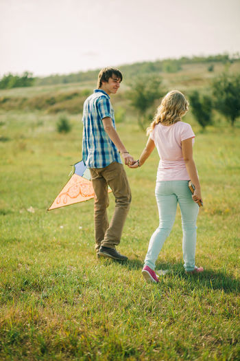 Full Length Of Man And Woman Walking On Grassy Field