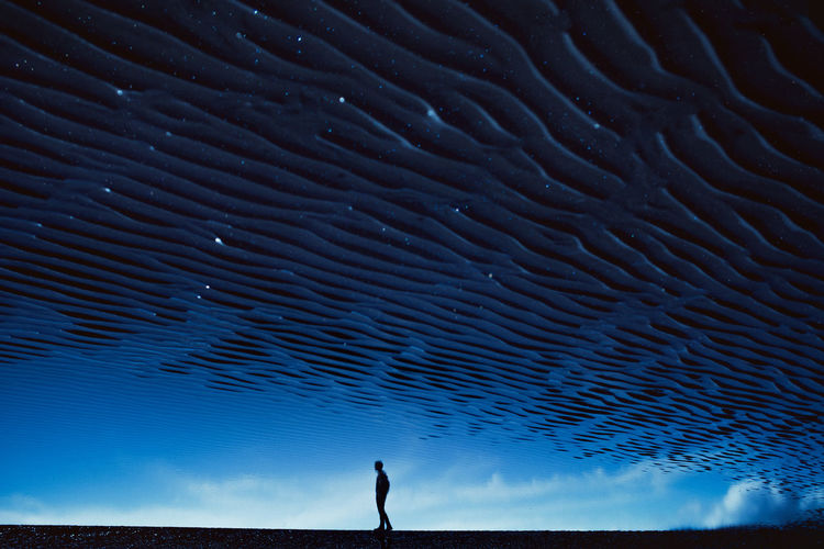 Silhouette person standing in sea against sky at night