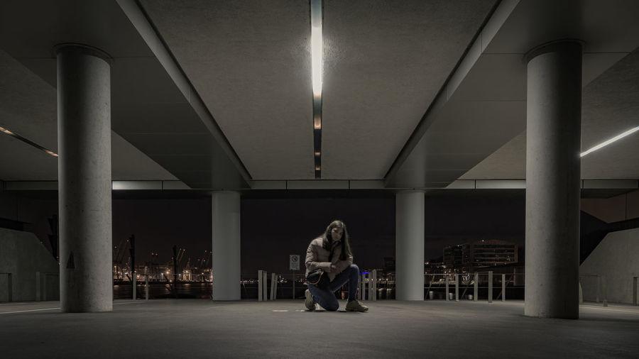 Portrait of girl kneeling in illuminated parking lot at night