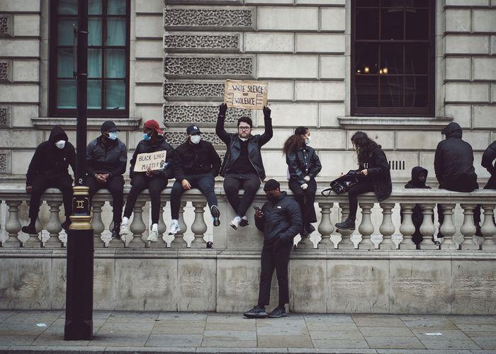 People standing on sidewalk against building in city