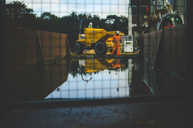 Built Structure Yellow Mode Of Transport Architecture Transportation Puddle Work Builders Builder Orange Tractor Reflection Land Vehicle People City Sky Adult Water Adults Only Outdoors Men Transportation Close-up Day Mode Of Transport