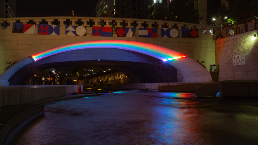 Illuminated bridge over canal by buildings at night