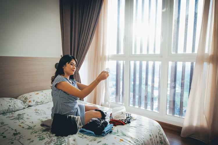 One Person Window Curtain Real People Full Length Furniture Indoors  Casual Clothing Lifestyles Young Adult Bed Home Interior Sitting Side View Leisure Activity Young Women Black Hair Day Hairstyle Contemplation Teenager