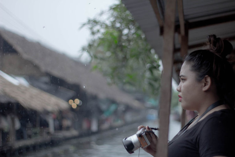 Side view of young woman holding camera during rainfall