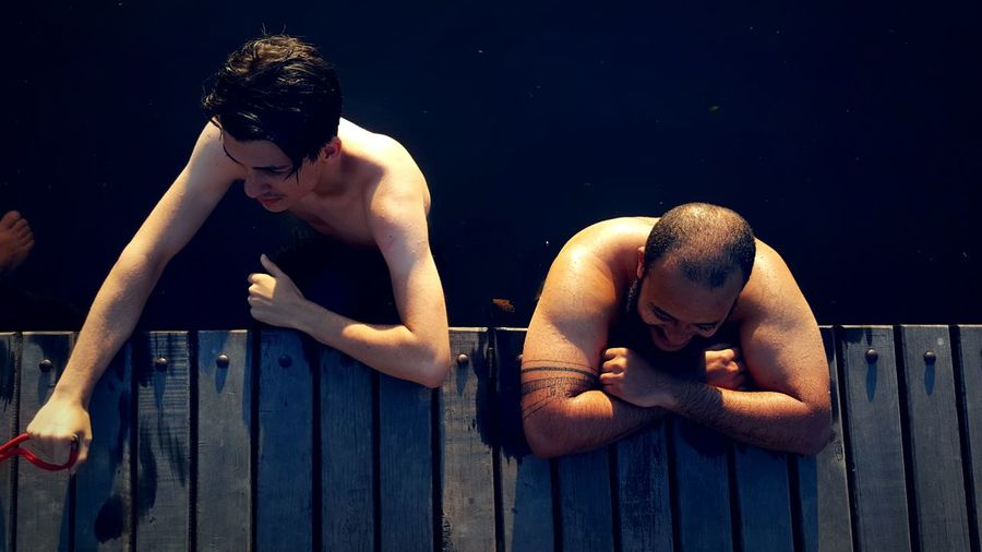 High Angle View Of Shirtless Male Friends Standing At Jetty In Lake
