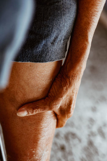 Midsection of woman touching leg in pain