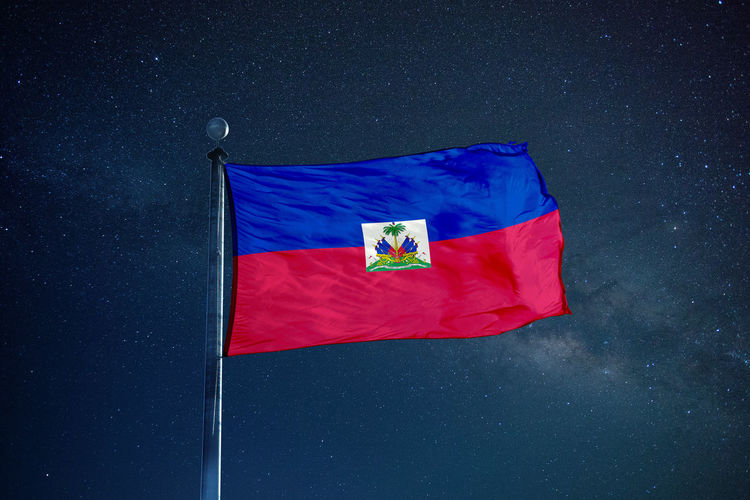 Low angle view of haiti flag against star field sky