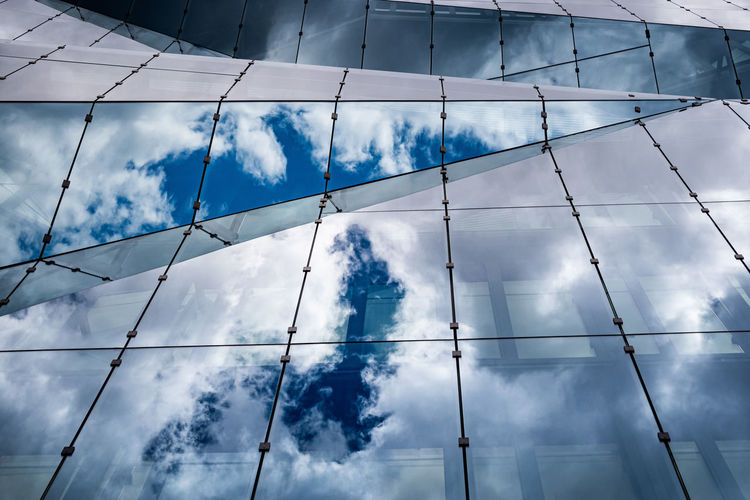 Glass building with reflection of cloudy sky