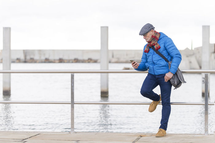 Senior man using a smarphone near the sea Calling Connectivity Hat Travel Blue Casual Clothing Connection Day Eyeglasses  Lifestyles Male Mammal Mobile One Person Outdoors Real People Sea Senior Seniors Smart Phone Technology Treavelling Trendy Using Phone Water