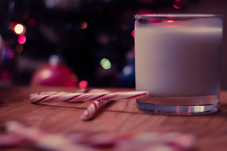 Close-Up Of Drink By Candy Canes In Glass On Table