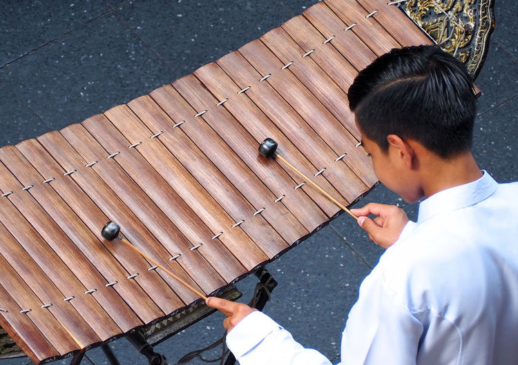 Thai xylophone played by thai people who weared white vintage traditional suit and top view camera. Real People One Person Young Adult Men Lifestyles Young Men Day Leisure Activity Holding High Angle View Wood - Material Headshot Outdoors Portrait Sunlight Standing Males  Occupation Effort Thai Xylophone Played By Thai People Who Weared White Vintage Traditional Suit And Top View Camera. Xylophone; Thai; Instrument; Music; Musical; Thailand; Traditional; Culture; Asian; Performance; Wooden; Classical; Background; Asia; Musician; Percussion; Art; Boy; Education; Playing; Wood; Entertainment; Sound; Oriental; Concert; Performer; Play; Child