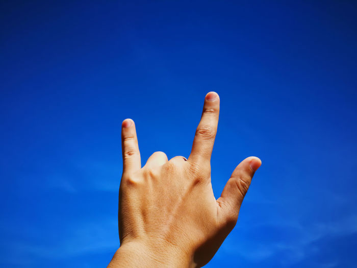 Man's hand make sign 'I LOVE YOU' on blue sky background. Love Blue Close-up Day Gesturing Human Body Part Human Finger Human Hand Nature One Person Outdoors People Personal Perspective Real People Sky Unrecognizable Person