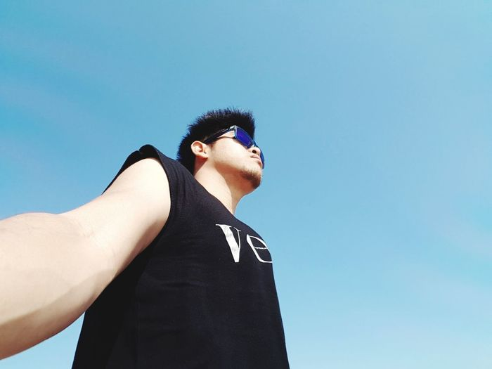 Low Angle View Of Man Wearing Sunglasses Against Blue Sky