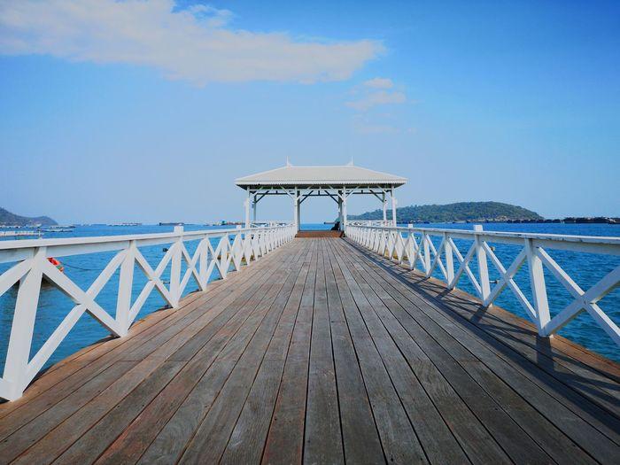 Wooden footbridge on pier against sky