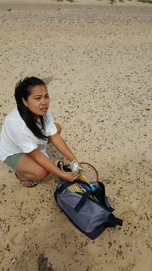 Portrait of woman with bag at sandy beach