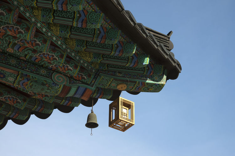 Low angle view of lantern hanging on roof of temple against clear blue sky