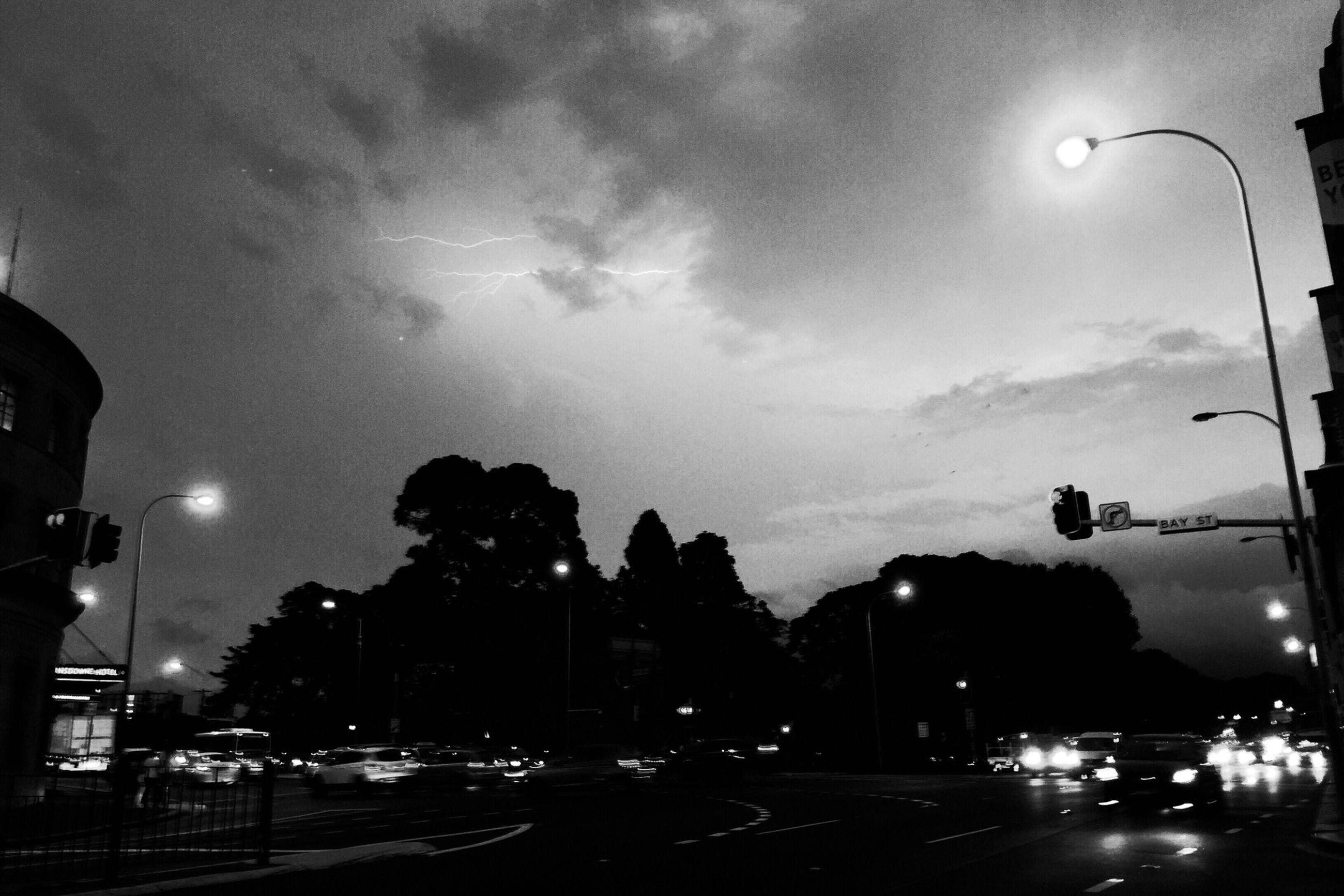 illuminated, street light, night, sky, lighting equipment, transportation, car, road, street, land vehicle, cloud - sky, silhouette, dusk, mode of transport, low angle view, outdoors, light - natural phenomenon, city, cloudy, city street