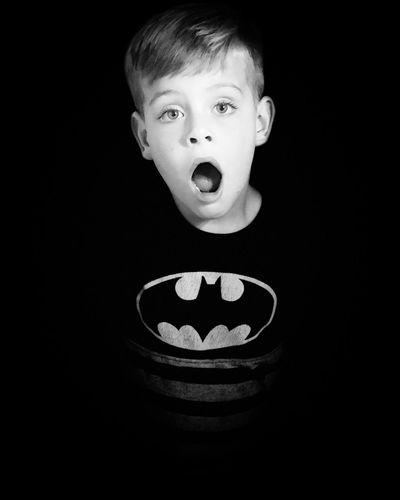 Portrait of boy against black background