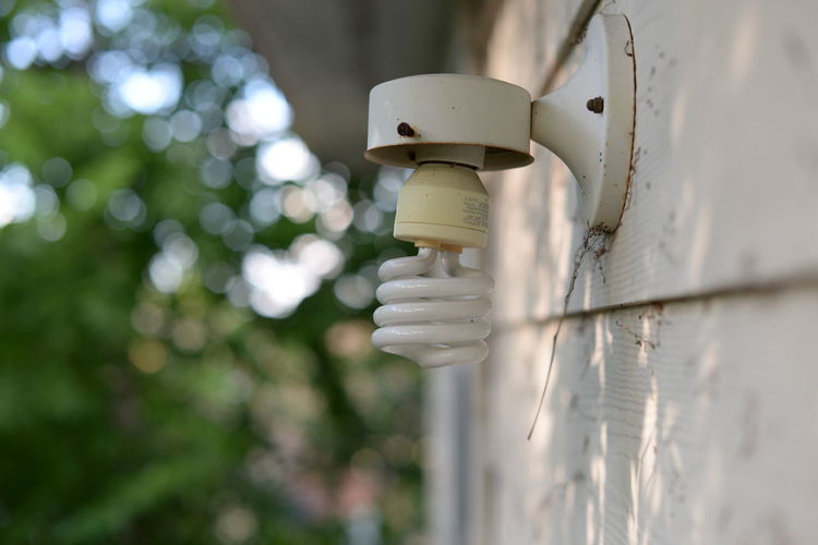 Close-up of energy efficient lightbulb attached on wall