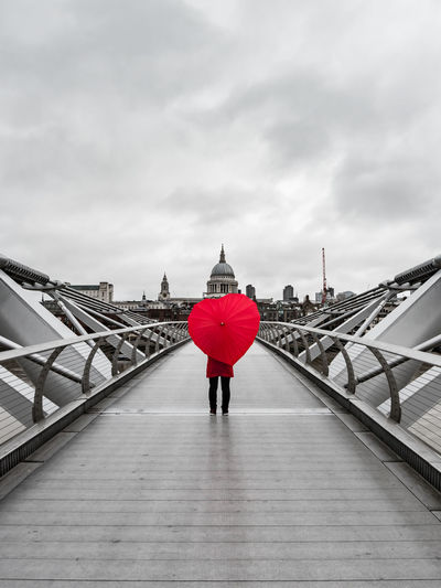 Rear view of woman with red heart shape umbrella standing on footbridge