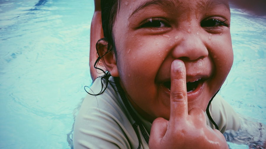 Close-up portrait of child with finger on lips in swimming pool