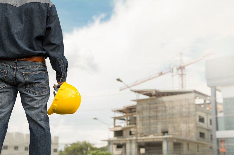 Midsection of architect standing at construction site against cloudy sky