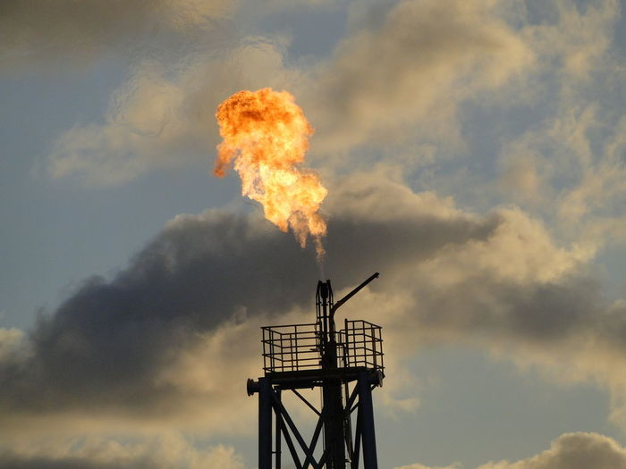 Oil refinery flare stack against cloudy sky